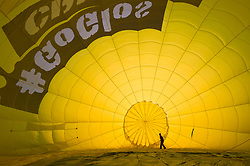 © Licensed to London News Pictures; 04/08/2021; Bristol, UK. Bristol International Balloon Fiesta - Fiesta Fortnight 2021. A balloonist makes final checks as a balloon is inflated prior to taking off. Fiesta Fortnight' sees its first mass balloon ascent on Wednesday, August 4 from Bristol's Elm Park. The Fiesta has never flown from this launch site before, and following a public survey, Elm Park was a hugely requested location to bring balloons. 'Fiesta Fortnight', will take place from Monday 2nd August to Sunday 15th August 2021 and will see hundreds of hot air balloons taking off from multiple locations across the city. The usual Bristol Balloon Fiesta event at Ashton Court is not happening this year because of the covid coronavirus pandemic. Photo credit: LNP.