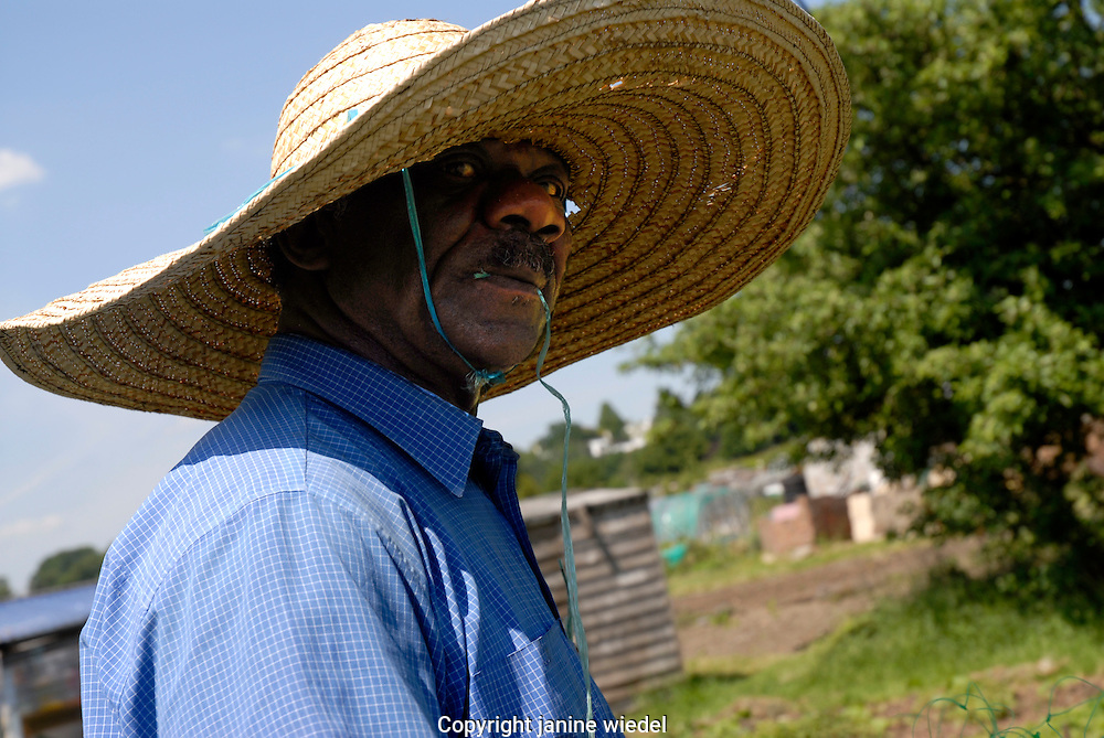 Man with large hat at Spa Hill allotment in Norwood in South London.
