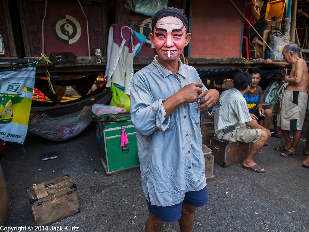 "18 AUGUST 2014 - BANGKOK, THAILAND: A  member of the Lehigh Leng Kaitoung Opera troupe relaxes backstage before a performance at Chaomae Thapthim Shrine, a small Chinese shrine in a working class neighborhood of Bangkok. The performance was for Ghost Month. Chinese opera was once very popular in Thailand, where it is called ""Ngiew."" It is usually performed in the Teochew language. Millions of Chinese emigrated to Thailand (then Siam) in the 18th and 19th centuries and brought their culture with them. Recently the popularity of ngiew has faded as people turn to performances of opera on DVD or movies. There are still as many 30 Chinese opera troupes left in Bangkok and its environs. They are especially busy during Chinese New Year and Chinese holiday when they travel from Chinese temple to Chinese temple performing on stages they put up in streets near the temple, sometimes sleeping on hammocks they sling under their stage. Most of the Chinese operas from Bangkok travel to Malaysia for Ghost Month, leaving just a few to perform in Bangkok.     PHOTO BY JACK KURTZ"