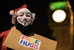 © Licensed to London News Pictures . 05/11/2016 . London , UK . A man wearing a Santa Claus outfit and an anonymous mask and carrying a FREE HUGS sign outside Parliament . Supporters of Anonymous , many wearing Guy Fawkes masks , attend the Million Mask March bonfire night demonstration , in central London . Photo credit : Joel Goodman/LNP