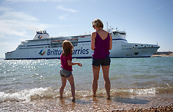 © Licensed to London News Pictures. 23/08/2019. Portsmouth, UK. Visitors to a beach at Portsmouth watch a ferry pass close by as they enjoy the sunshine. Record high temperatures are expected in parts of the United Kingdom over the three day bank holiday weekend. Photo credit: Peter Macdiarmid/LNP