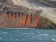 Volcanic ash layers erode from a sea cliff. In the South Shetland Islands near the Antarctic Peninsula, Deception Island has one of the safest harbors in Antarctica. Deception Island is the caldera of an active volcano, which caused serious damage to local scientific stations in 1967 and 1969. The island previously held a whaling station and is now a tourist destination and scientific outpost, with research bases run by Argentina and Spain. The island is administered under the Antarctic Treaty System. The surrounding sea is closed by ice from early April to early December.