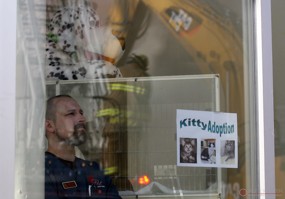 9/13/13--Winona<br /> Brandon Hatten, a veteranary tech at a pet hospital, watches firefighters battle a fire from across the street in downtown Winona, Minn., Friday Sept. 13, 2013. The fire destroyed three buildings and forced officials to evacuate the entire block. (Photo for MPR News by Alex Kolyer)