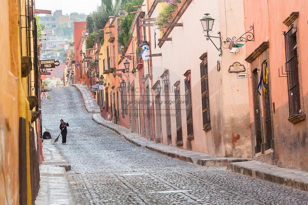A woman sweeps the cobblestones along Cuadrante Street in the historic center of San Miguel de Allende, Mexico.