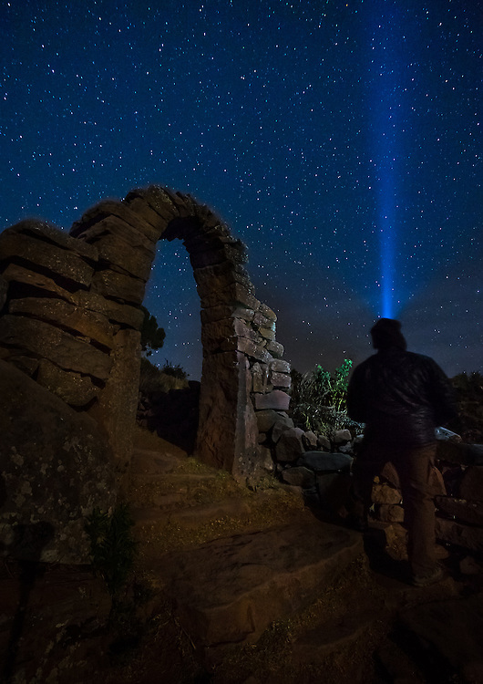 PUNO, PERU - CIRCA OCTOBER 2015:  Man looking the sky and stars by a typical arch of the Island of Taquile in Lake Titicaca.