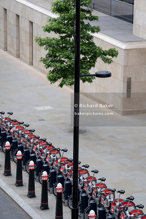 An urban landscape of cycle lane, pavement and the security docks of Santander rental bikes on the Farringdon Road in the City of London, the capital's financial district, on 24th June 2021, in London, England. The vertical line of a lamp post has merged with the trunk of a street tree. (Photo by Richard Baker / In Pictures via Getty Images) CREDIT RICHARD BAKER.