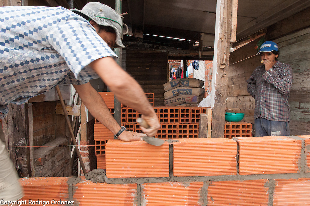 Víctor Morel (left) lays bricks for a new construction. In Ocho de Mayo, precarious houses with brick walls stand next to shacks of wood planks and asbestos.