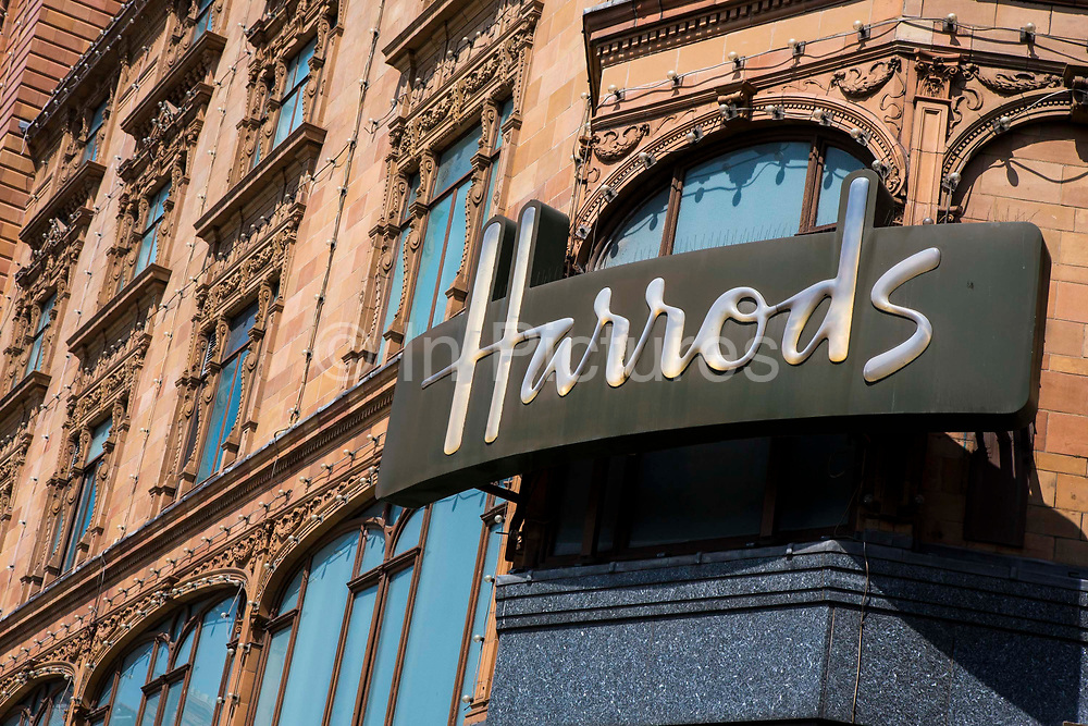 The iconic Harrods sign on the store building in Knightsbridge, London, United Kingdom.