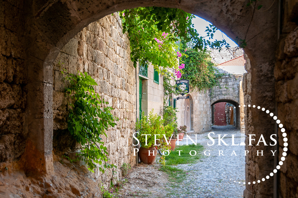 Rhodes. Greece. Arched pebbly laneway leading to a hotel pension with green plants at its entrance inside the old town. The old town is a UNESCO world heritage listed site and the best preserved, oldest and largest living medieval city in Europe. The 4km defensive walls were built by the Knights of St John during the 13th to 15th century to defend Western Europe against the expanding Ottoman Empire. Within the walls are a medieval warren of small alleyways and magnificent historical buildings. The island of Rhodes is the largest of the Dodecanese Island group and one of the most popular Greek Islands.
