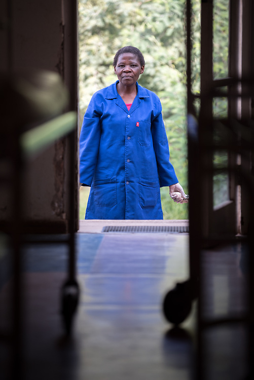 """2 March 2017, Morija, Maseru district, Lesotho: Matabo Mosoeu is a cleaner at Scott Hospital. Scott Hospital is run by the Lesotho Evangelical Church in Southern Africa and is a founding member of the Christian Health Association of Lesotho. It is located in the village of Morija, and operates and supervises clinics in the Maseru District of Lesotho. Scott started out as a dispensary in 1864, and today offers comprehensive healthcare Mondays-Fridays, as well as pharmaceutical services around the clock. Lesotho suffers from high numbers in Tuberculosis in disesase and mortality, and so the hospital screens all patients for TB. The hospital observes among many patients what they describe as """"low health-seeking behaviour"""", services are increasing and demand rising, but space and human resources are a challenge, as is funding. I key concern is one of infrastructure, where the original design of the hospital matches poorly with current needs, as departments and buildings are scattered, posing a challenge for security. Another challenge is to adapt donation structures, so as to be able to receive payments electronically. The hospital has one ambulance, which they describe as not enough, but what they have. Another challenge is that lack of funds affects maintenance of buildings and infrastructure, as the immediate care of patients take priority. PLEASE NOTE: This photo is not to be used in social media."""