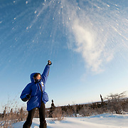 Maddy Ewins throws a cup of hot water in to the frigid -20 Farenheit air.  Wapusk National Park, Manitoba, Canada