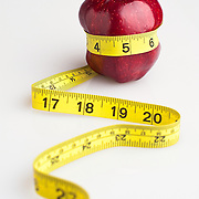 Red delious apple with tape measure rapped around thin waist.