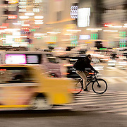 A cyclist speeds through the Shibuya crossing in Tokyo.