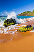 Surf crashing on lava rocks at Secret Beach (Kauapea Beach), Kilauea Lighthouse visible, Island of Kauai, Hawaii