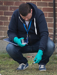 © Licensed to London News Pictures. 12/04/2017. London, UK. A detective collects evidence near an alleyway off Newnham Close where a 19 year old man, named locally as Abdullahi Tarabai,  was murdered yesterday after reportedly being chased though a housing estate in Northolt. This is the second fatal stabbing in the capital in 24 hours. The location is adjacent to a gun siege from October 2016. Four men have been arrested Photo credit: Peter Macdiarmid/LNP