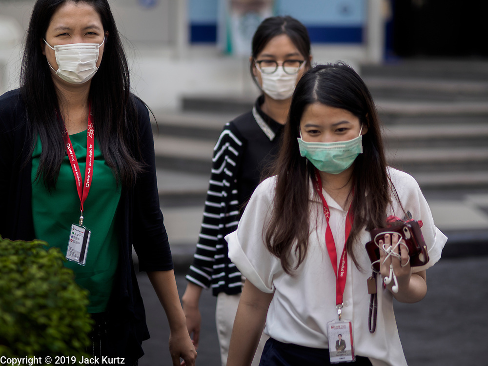 """14 JANUARY 2019 - BANGKOK, THAILAND:       Women wearing breathing filters on the street in Bangkok. Bangkok has been blanketed by heavily polluted air for almost a week. Monday morning, the AQI (Air Quality Index) for Bangkok  was 182, worse than New Delhi, Jakarta, or Beijing. The Saphan Kwai neighborhood of Bangkok recorded an AQI of 370 and the Lat Yao neighborhood recorded an AQI of 403. An AQI above 50 is considered unsafe. Public health officials have warned people to avoid """"unnecessary"""" outdoor activities and wear breathing masks to filter out the dust.   PHOTO BY JACK KURTZ"""