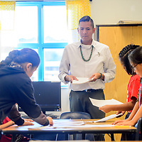 Apache County Rural School Teacher of the Year Duane Yazzie hands out a reading exercise to students at Tséhootsooi Diné Bi Ołta' School in Window Rock Wednesday.