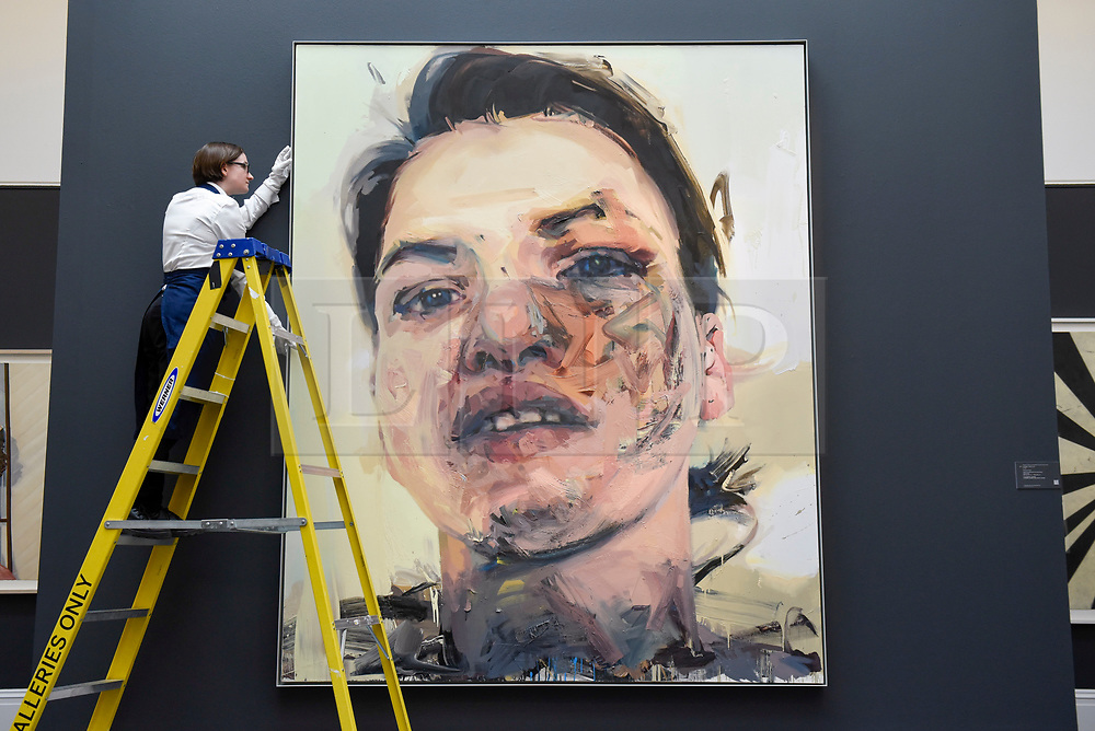 """© Licensed to London News Pictures. 21/06/2019. LONDON, UK. A technician inspects """"Shadow Head"""", 2007-2013, by Jenny Saville (Est. GBP 3-5m) at the preview of a Contemporary Art auction at Sotheby's New Bond Street.  The sales take place 26 and 27 June 2019.  Photo credit: Stephen Chung/LNP"""