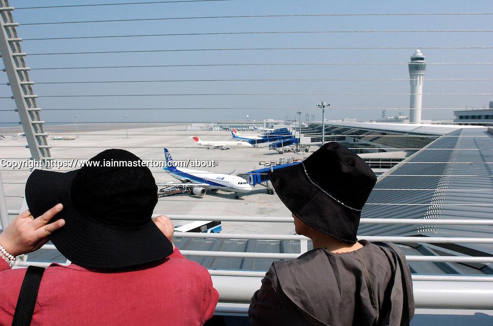 Women watch aircraft at New Central Japan International Airport in Nagoya Japan
