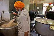 A Sikh pours chai into a metal container that keeps it hot. Everyday 600 kilograms of sugar and 20 of tea leaves are used to make the traditional indian tea. A large tin is full of milk, kept warm available for baby's bottles.