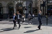 Strangers to and fro in a sunny City of a London street corner. Businessmen walk during lunchtime, in conversation with associates and strangers in their own space. In an almost cinematic moment of street corner life, we see reflected light from nearby plate glass office buildings that fill in shadows and darker places in the capital's financial heart - the City of London, known as the Square Mile, founded by the Romans in AD43.