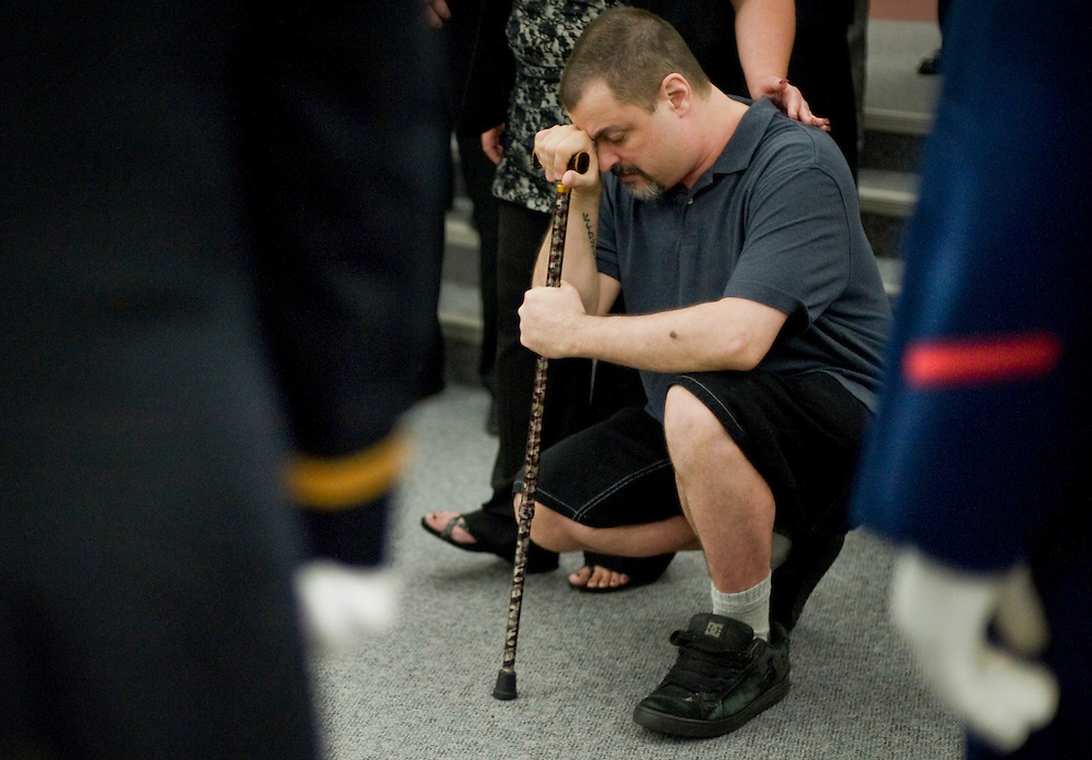 James Pratt of Southington, brother of Army Spec. Dennis Pratt kneels during a dedication ceremony for the Connecticut Wall of Honor to pay tribute to the Connecticut men and women who lost their lives in Iraq and Afghanistan at the Capitol in Hartford, Conn., Thursday, May 24, 2012. Seven soldiers were added to the wall. (AP Photo/Jessica Hill)