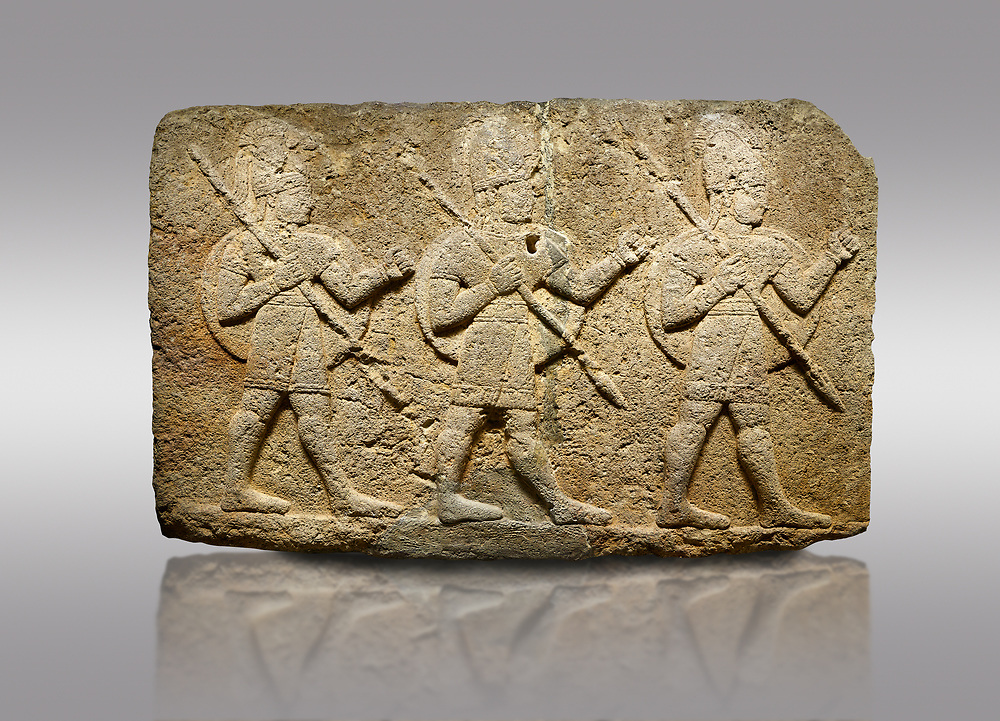 Picture & image of Hittite monumental relief sculpted orthostat stone panel of Herald's Wall Basalt, Karkamıs, (Kargamıs), Carchemish (Karkemish), 900-700 B.C. Anatolian Civilisations Museum, Ankara, Turkey.<br /> <br /> Military parade. Two helmeted soldiers in short skirts carry the shield on their backs and the spears in their hands. <br /> <br /> Against a gray background. .<br />  <br /> If you prefer to buy from our ALAMY STOCK LIBRARY page at https://www.alamy.com/portfolio/paul-williams-funkystock/hittite-art-antiquities.html  - Type  Karkamıs in LOWER SEARCH WITHIN GALLERY box. Refine search by adding background colour, place, museum etc.<br /> <br /> Visit our HITTITE PHOTO COLLECTIONS for more photos to download or buy as wall art prints https://funkystock.photoshelter.com/gallery-collection/The-Hittites-Art-Artefacts-Antiquities-Historic-Sites-Pictures-Images-of/C0000NUBSMhSc3Oo
