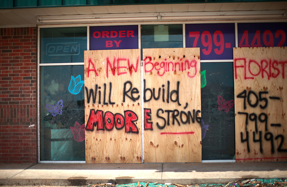 A sign protects broken windows at a tornado-damaged store in Moore, Oklahoma May 23, 2013. The tornado was the strongest in the United States in nearly two years and cut a path of destruction 17 miles long and 1.3 miles wide. REUTERS/Rick Wilking (UNITED STATES)