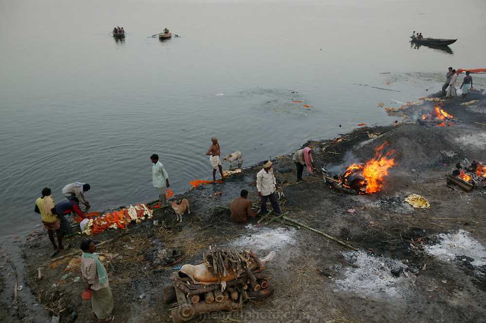 Male family members carry a body to the edge of the Ganges River for a final ritual dip before cremation at the Harishchandra Ghat in Varansi, India. Other fires burn bodies that have already had their cremation ritual.
