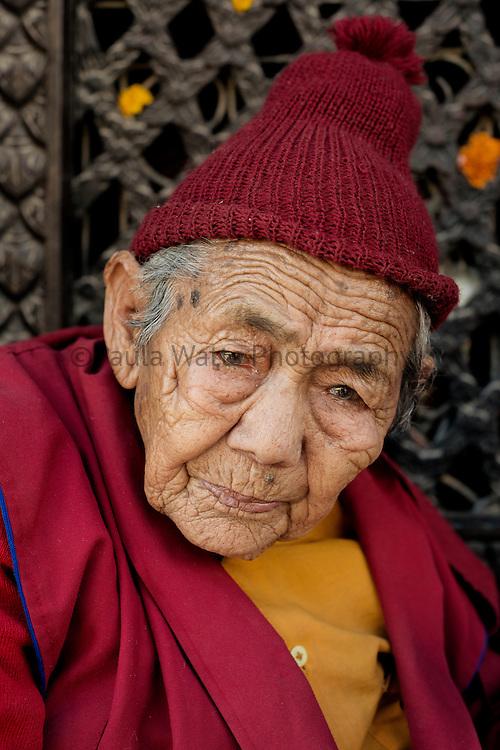 Elderly nun in Kathmandu Nepal near Boudha Stupa.