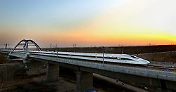 """File photo taken on Nov. 25, 2012 shows a bullet train running through the Huanghe Bridge on Zhengzhou section of the Beijing-Guangzhou high-speed railway in central China's Henan Province. """"Building more high-speed railways"""" has been a hot topic at the annual sessions of China's provincial legislatures and political advisory bodies intensively held in January. China has the world's largest high-speed rail network, with the total operating length reaching 19,000 km by the end of 2015, about 60 percent of the world's total. The expanding high-speed rail network is offering unprecedented convenience and comfort to travelers, and boosting local development as well. Chinese companies have developed world-leading capabilities in building high-speed railways in extreme natural conditions. High-speed railway routes across China have been designed to suit its varying climate and geographical conditions. The Harbin-Dalian high-speed railway travels through areas where the temperature drops to as low as 40 degree Celsius below zero in winter, the Lanzhou-Xinjiang railway passes through the savage Gobi Desert and the Hainan Island railway can withstand a battering from typhoons. The China Railway Corp. plans to spend another 800 billion yuan (around 120 billion U.S. dollars) in 2016, especially in less-developed central and western regions. EXPA Pictures © 2016, PhotoCredit: EXPA/ Photoshot/ Zhu Qing<br /><br />*****ATTENTION - for AUT, SLO, CRO, SRB, BIH, MAZ only*****"""