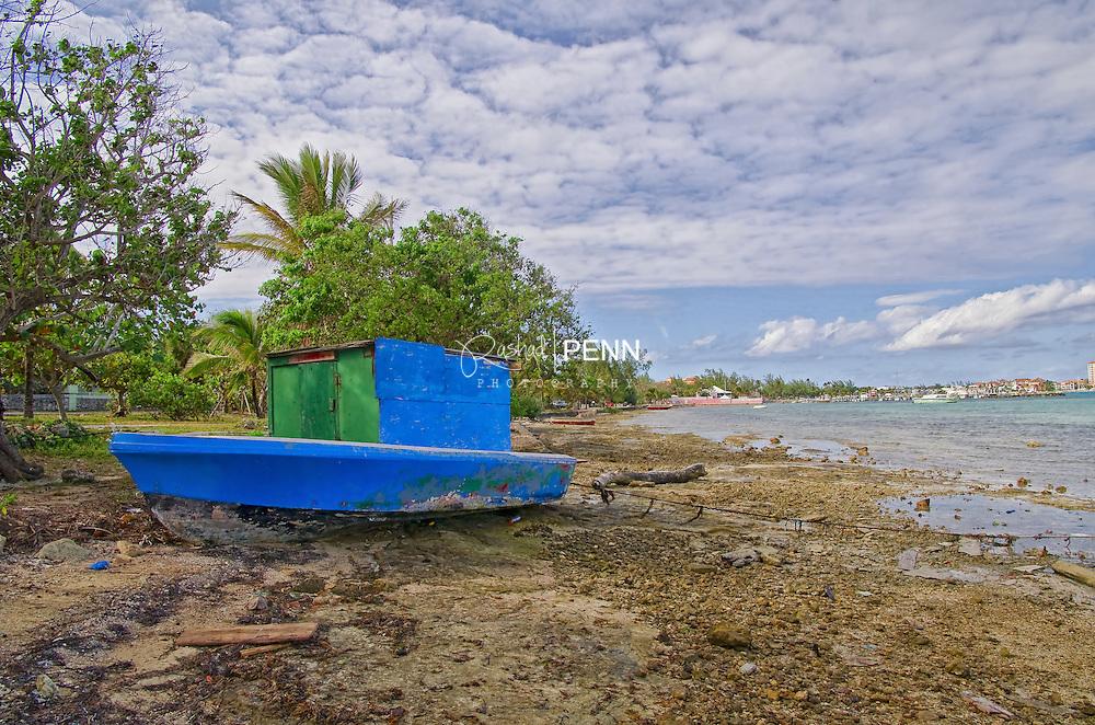 A small boat house locked on land near the sea.