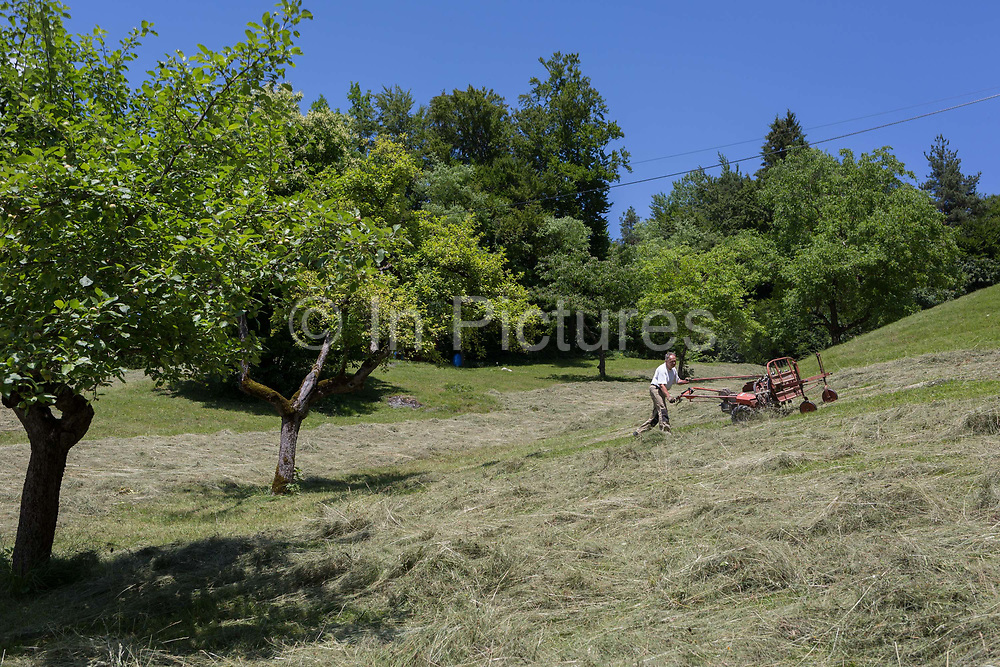 Using a powered agricultural mower, local man mows grass on a hillside meadow, on 18th June 2018, in Kupljenik, Slovenia.