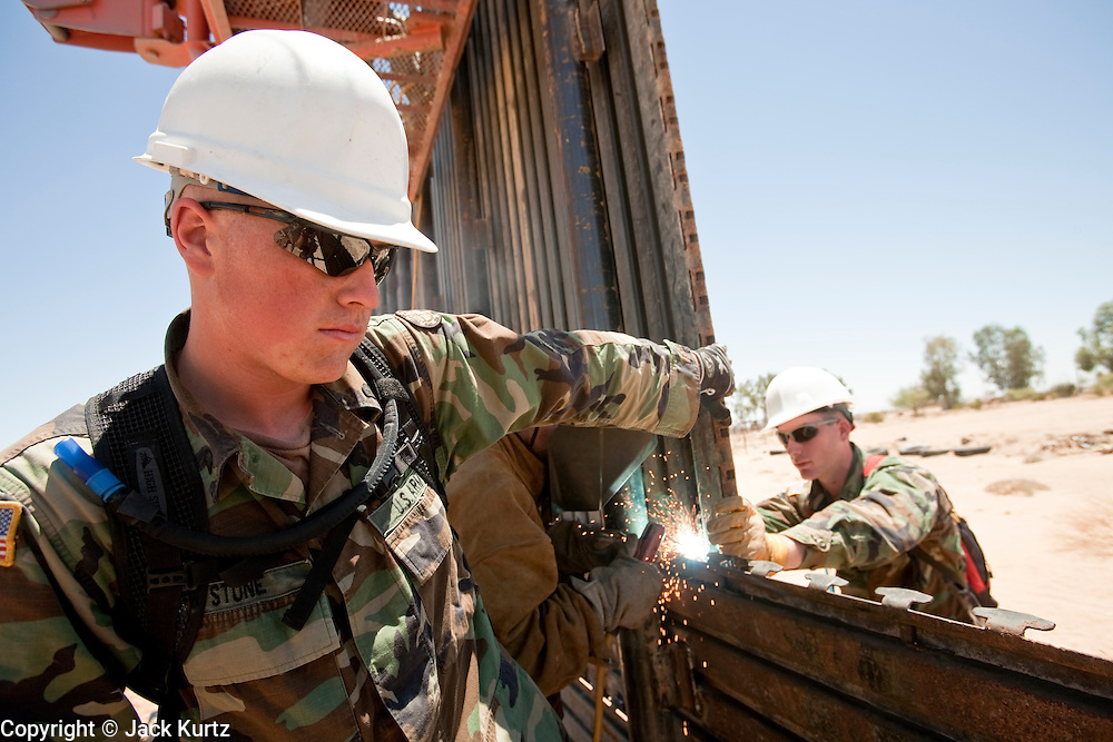 12 JUNE 2006 - SAN LUIS, AZ: Soldiers from the Utah Army National Guard work on a section of fence on the US/Mexico border near San Luis, AZ, Monday. Fifty five members of the 116th Engineer Company, Combat Support Engineers, of the Utah Army National Guard are in San Luis, AZ, to build a fence and improve roads east of the San Luis Port of Entry on the US/Mexico border. The unit is the first of an estimated 6,000 US military personnel, almost all of them Army National Guard, who will be dispatched to the US/Mexico border by President Bush to help control immigration on the border. The Guardsmen will primarily build roads and fence and staff surveillance centers. They will not be engaged in first line law enforcement work.  Photo by Jack Kurtz