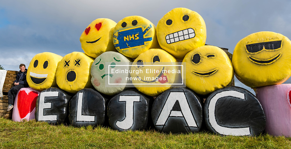 Athelstaneford, East Lothian, Scotland, United Kingdom, Bale Art 2020: East Lothian Junior Agricultural Club's bale art in support of charity RSABI, which supports people from Scottish agriculture emotionally, practically and financially. The yellow bale material was also bought in support of a children's cancer research charity. The theme this year is #keeptalking. Pictured: Hamish Logan, one of the young farmers who constructed the bale art.<br /> Sally Anderson | EdinburghElitemedia.co.uk
