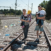 Afternoon, Sunday 13 September 2015. Aysha walks on the railway line towards the Greek - Macedonian border. An unknown to her Syrian man helps her by carrying Bisan in his arms.