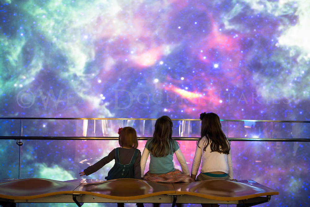 The SECU Daily Planet projection screen at the North Carolina Museum of Natural Sciences explodes with colorful visuals of the universe as, pictured left to right, Catrin Williams, 4, Heather Cameron, 4 and Delwyn Williams, 5, who all reside in Cary, watch with amazement on Jan. 28. With today's weather calling for temperatures to hover around 30 degrees, followed by snow, coupled with school cancellations, most of the Triangle community chose to remain indoors.