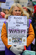 A woman with a WASPI Women Against State Pension Inequality at the Bread and Roses Womens March on January 19, 2019 in London, England.  The event was dubbed the Bread and Roses March based on the strikes of the same name by textile workers in Massachusetts in 1912 and Bread and Roses is the title of a poem by American poet James Oppenheim about the strikes.