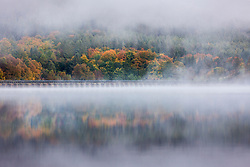 © Licensed to London News Pictures. 13/10/2020. Derwent UK. The morning mist & trees reflect into the calm water of Ladybower reservoir this morning in Derbyshire. Photo credit: Andrew McCaren/LNP