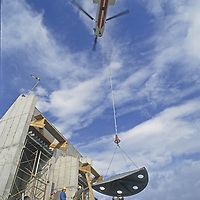 A massive Boeing Chinook helicopter lifts concrete and heavy steel used to  assemble a tram station atop 11,166-foot Lone Mountain at Montana's Big Sky Ski Area - a difficult and dangerous project.