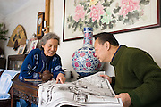 Couple read a newspaper story about the Beijing Olympic Games, in their home in the Hutongs area, Beijing, China