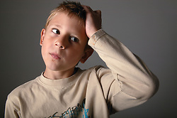 Portrait of a young boy looking puzzled,
