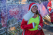 The finish brings relief and a shower of 'snow' - Thosuands of runners, of all ages, in santa suits and other Christmas costumes runaround Clapham Common for Great Ormond Street Hospital and for fun. London 30 Nov 2016