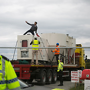 Anti-fracking  activists and protesters outside the gates of Quadrilla's fracking site June 31st, Lancashire, United Kingdom. An activists got on the truck which kept moving and took hin inside the Quadrilla perimeter. The struggle against fracking in Lancashire has been going on for years. The fracking company Quadrilla is finally ready to bring in a drill tower to start drilling and anti-frackinhg activists are waiting in front of the gates to block the equipment getting in. Fracking is a destructive and potential dangerous and highly contentious method of extracting gas and this site will be the first of many in the United Kingdom reaching miles out under ground.