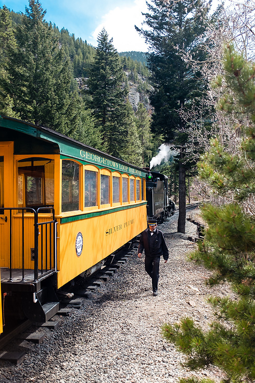 A Georgetown Loop Railroad conductor returns from checking a historic steam engine upon arrival into Devil's Gate Depot.