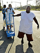 Candice Victor (L) who said she was in labor with a breech baby is pulled down the street on a lumber cart by her husband Janiero in New Orleans East August 31, 2005. Authorities struggled on Wednesday to evacuate thousands of people from hurricane-battered New Orleans as food and water grew scarce and looters raided stores, while U.S. President George W. Bush said it would take years to recover from the devastation. REUTERS/Rick Wilking