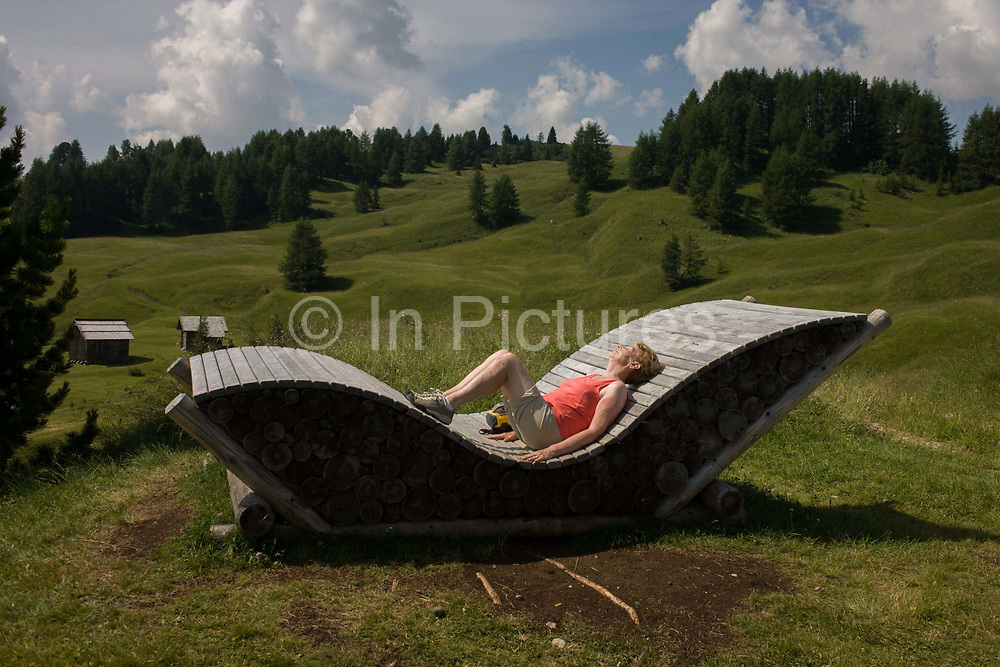 Rest seat made from logs in the Pralongià above San Cassiano-St. Kassian in the Dolomites, south Tyrol, northern Italy. In winter, the Pralongià meadows are the heart of Alta Badia's skiing area. With the backdrop of mountain peak panoramas and forests, this is known as the Movimënt where activities for families with young people can play, exercise and general experience the great outdoors at 2,000 metres above sea level between the towns of La Villa, San Cassiano and Corvara in the Alta Badia area of south Tyrol.