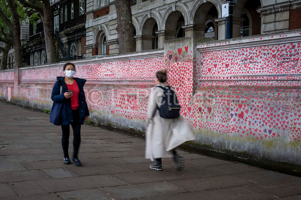 Two people walk past the National Covid memorial wall, a sea of red love hearts remembering all those who have died due to the COVID-19 pandemic on the 25th of May 2021 on the south bank in London, United Kingdom. Over 150,000 people have lost their lives in the United Kingdom due to the pandemic, the wall is a space for them to be remembered.