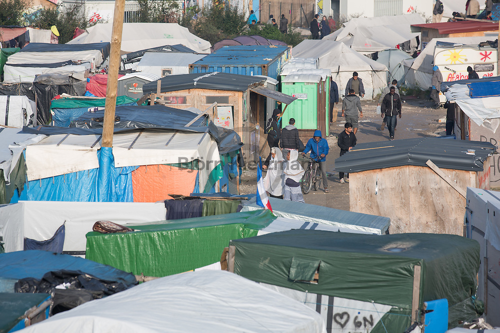 """Calais, Pas-de-Calais, France - 23.10.2016    <br />  <br /> Last day of the of the so called """"Jungle"""" refugee camp on the outskirts of the French city of Calais before the scheduled eviction. Many thousands of migrants and refugees are waiting in some cases for years in the port city in the hope of being able to cross the English Channel to Britain. French authorities announced that they will shortly evict the camp where currently up to up to 10,000 people live.<br /> <br /> Letzter Tag des sogenannten """"Jungle"""" Fluechtlingscamp am Rande der franzoesischen Stadt Calais vor der angesetzten Raeumung. Viele tausend Migranten und Fluechtlinge harren teilweise seit Jahren in der Hafenstadt aus in der Hoffnung den Aermelkanal nach Großbritannien ueberqueren zu koennen. Die franzoesischen Behoerden kuendigten an, dass sie das Camp, indem derzeit bis zu bis zu 10.000 Menschen leben Kürze raeumen werden. <br /> <br /> Photo: Bjoern Kietzmann"""