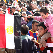 A young man carries his flag-waving brother through Cairo's Tahrir Square as they celebrate the Day of Justice and Cleansing.